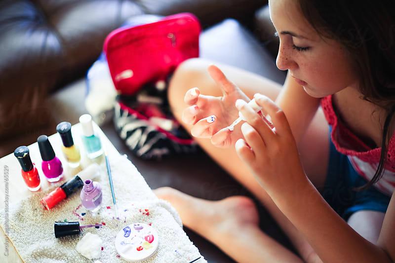 Girl giving herself a manicure by Carolyn Lagattuta for Stocksy United
