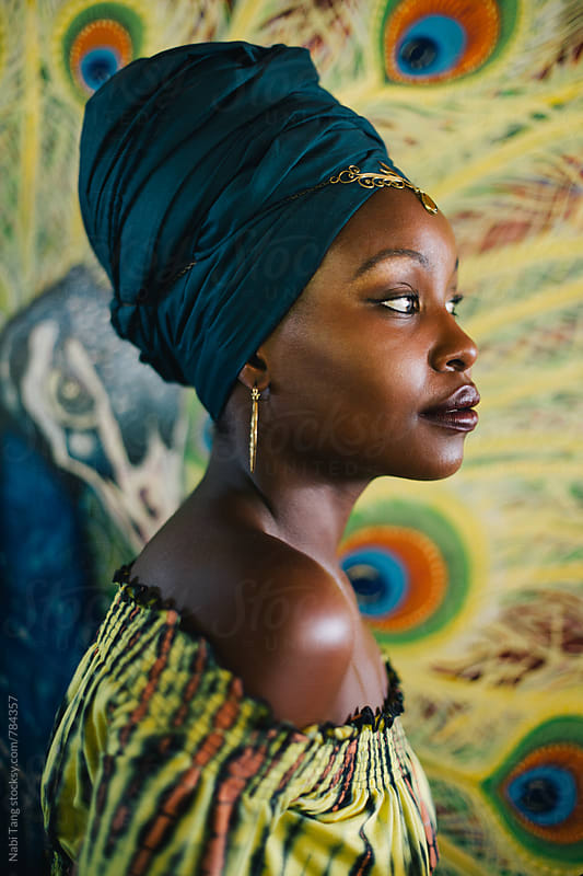 Beautiful african hippie profile in front of peacock painting background by Nabi Tang for Stocksy United
