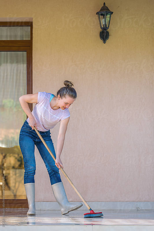 Young woman scrubbing the terrace floors  by RG&B Images for Stocksy United