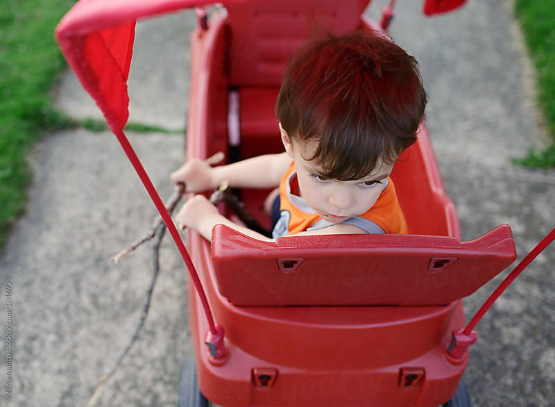 child looks out back of wagon by Maria Manco for Stocksy United