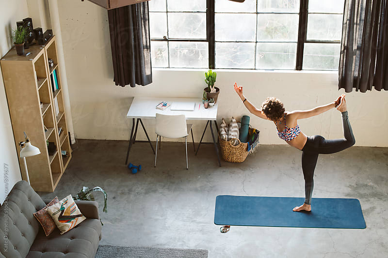 Shot of woman from above doing yoga in her loft apartment. by Kate Daigneault for Stocksy United