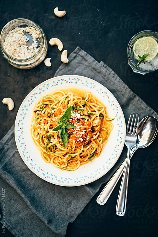 Food: Zucchini spaghetti with herbed tomato Sauce and ground cashew nuts by Ina Peters for Stocksy United