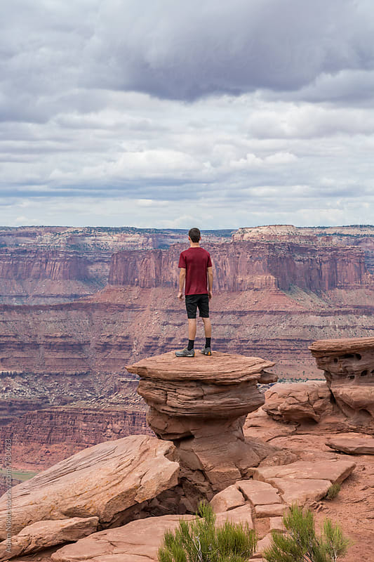 Teenage boy standing a rock pillar looking out over a vast landscape by Adam Nixon for Stocksy United