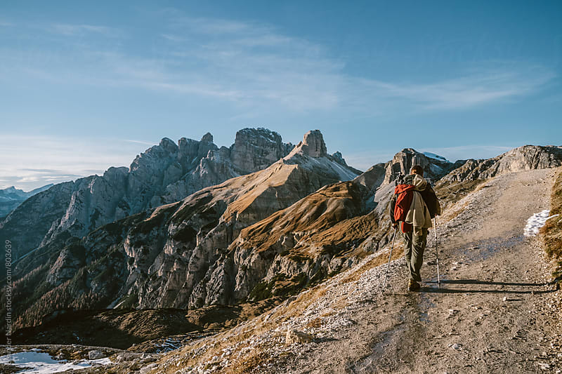 alpine hiker walking in the italian dolomites in autumn by Leander Nardin for Stocksy United