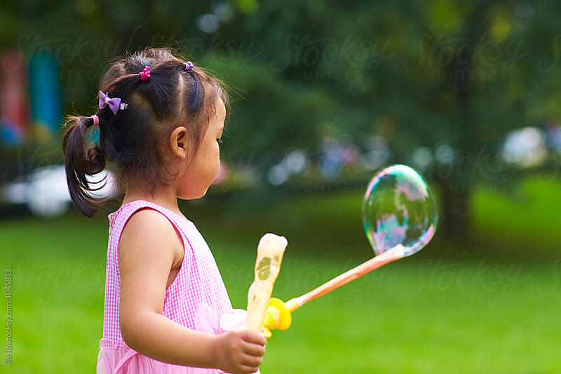 happy kid playing soap bubble outdoor in the park by Bo Bo for Stocksy United