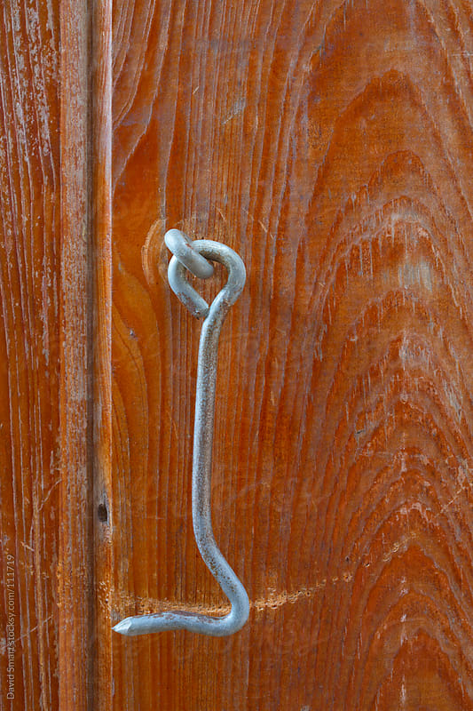 Hook type door latch on a rustic cabin door by David Smart for Stocksy United