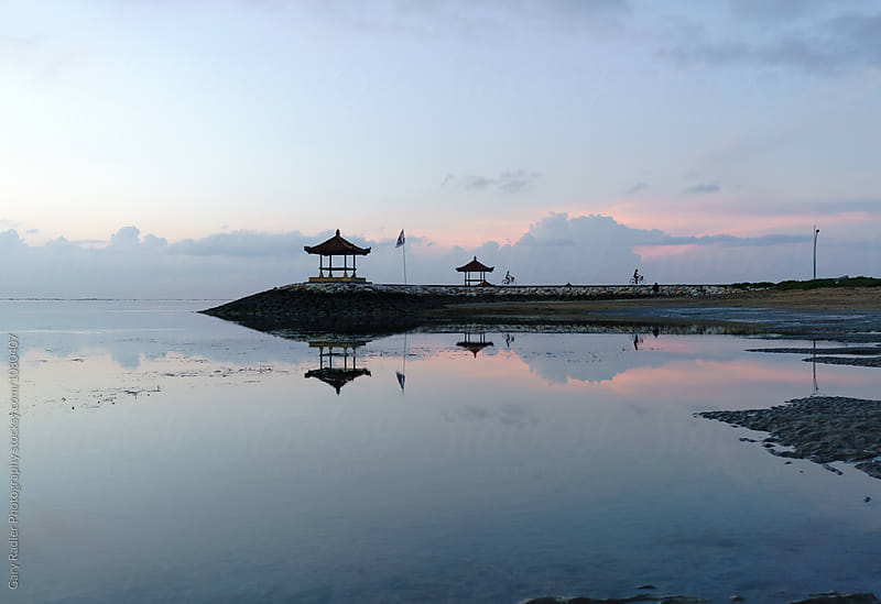 Two Cyclists Riding to Shore from Meditation Hut, Sanur, Bali by Gary Radler Photography for Stocksy United