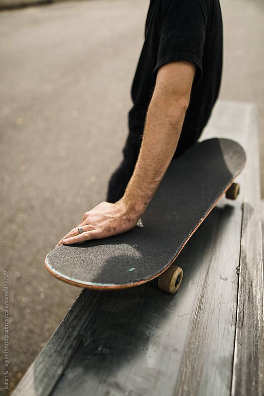 Man sitting on skateboard by Isaiah & Taylor Photography for Stocksy United
