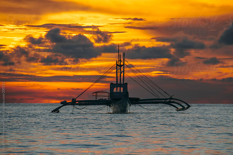 Traditional asian fishing boat on the sea at sunset by Alejandro Moreno de Carlos for Stocksy United