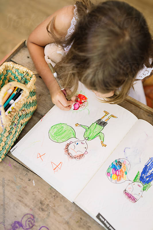 Little Girl Drawing at home by Alberto Bogo for Stocksy United