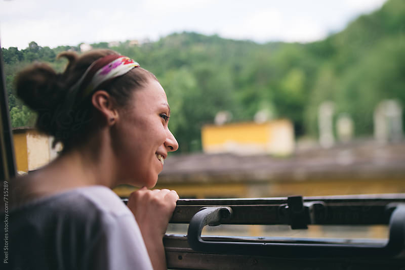 Young woman sticking her head out of train window by Pixel Stories for Stocksy United