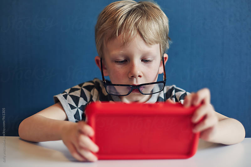 Child using an electronic tablet by sally anscombe for Stocksy United