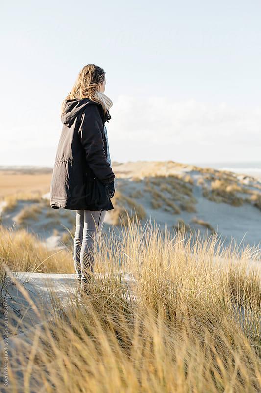 Woman on top of some dunes looking at the coast. by Koen Meershoek for Stocksy United