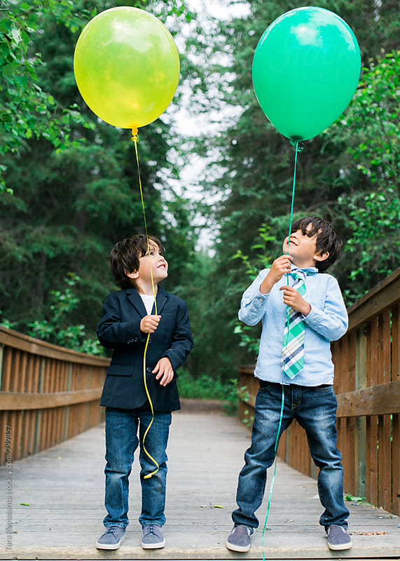 two young boys looking up at their helium balloons by Tara Romasanta for Stocksy United