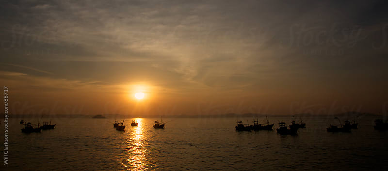 Fishing boats sit at anchor in the sunrise by Will Clarkson for Stocksy United