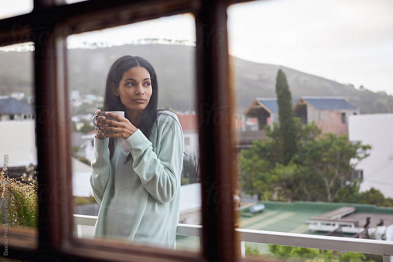beautiful young woman with coffee outdoors  on the balcony by Daxiao Productions for Stocksy United