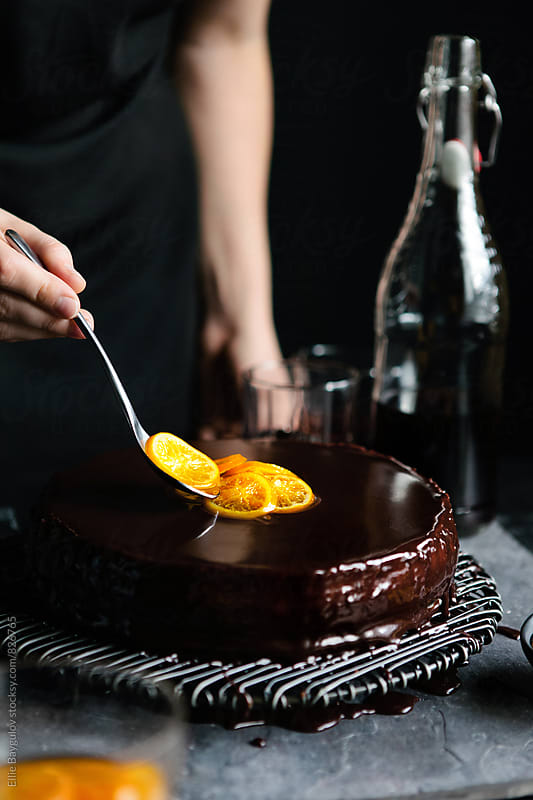 Woman topping cake with candid oranges by Ellie Baygulov for Stocksy United