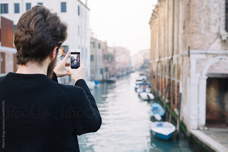 Young man taking a photo with his cell in the street by Alberto Bogo for Stocksy United