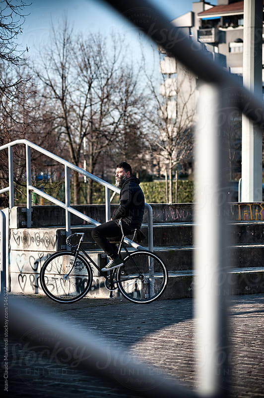 Hipster man takes a break with his fixed gear bike in a suburb area of Milano by Jean-Claude Manfredi for Stocksy United