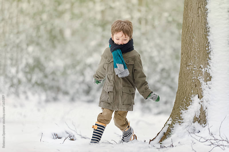 Boy playing in snow woodland by Rebecca Spencer for Stocksy United