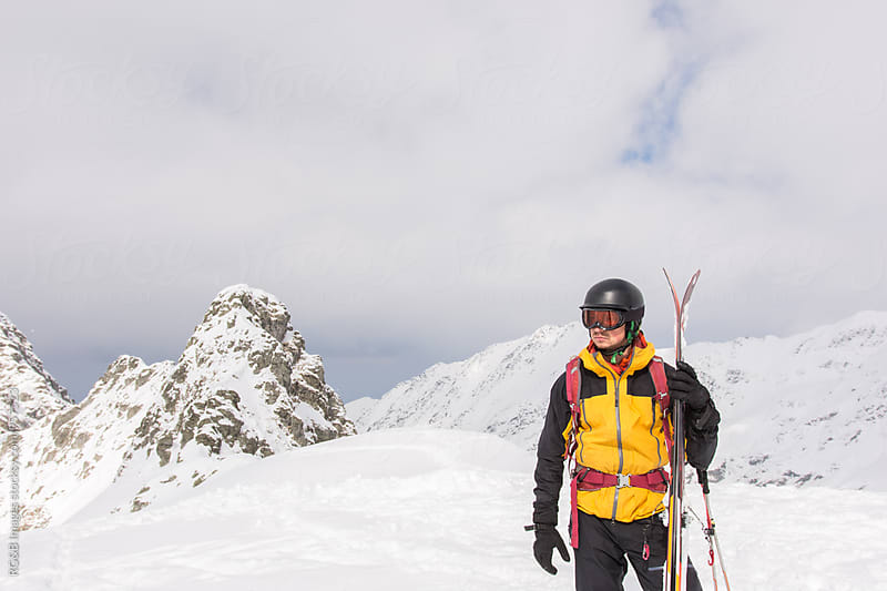 Portrait of skier holding his skis by RG&B Images for Stocksy United