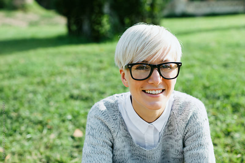 Blonde woman wearing rimmed glasses sitting on the park. by BONNINSTUDIO for Stocksy United