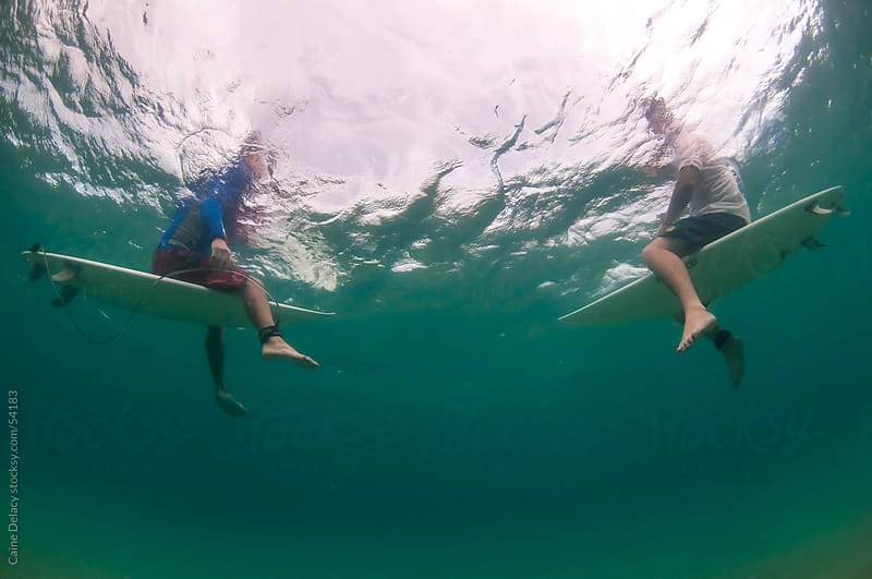 Sitting on Surf boards in the water, shot from underwater looking up. by Caine Delacy for Stocksy United
