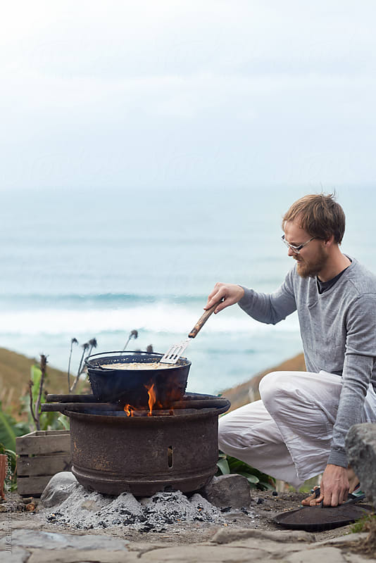 Cooking with fire outdoors by ocean  by Jill Chen for Stocksy United