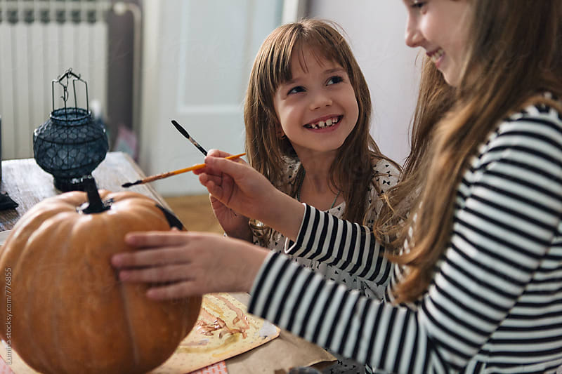 Sisters Decorating a Pumpkin for Halloween  by Lumina for Stocksy United