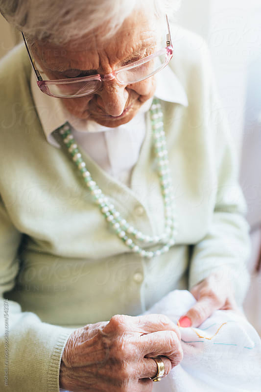 Old woman embroidering at home by michela ravasio for Stocksy United