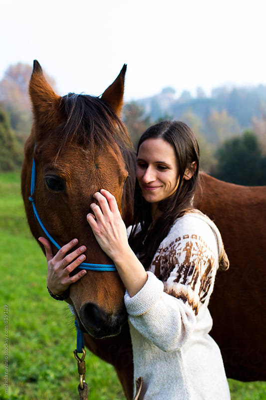 Smiling woman caressing her horse by michela ravasio for Stocksy United