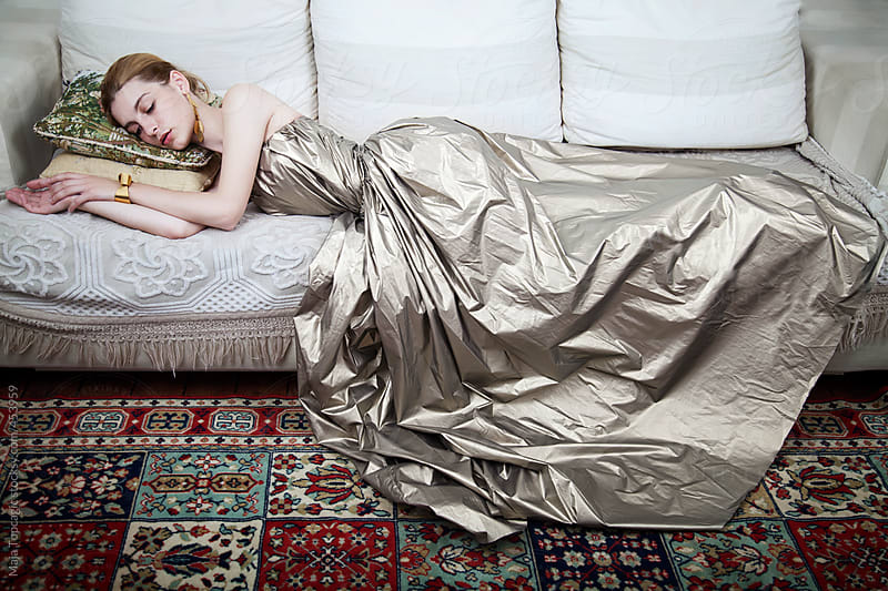 Young beautiful woman in a dress lying down by Maja Topcagic for Stocksy United
