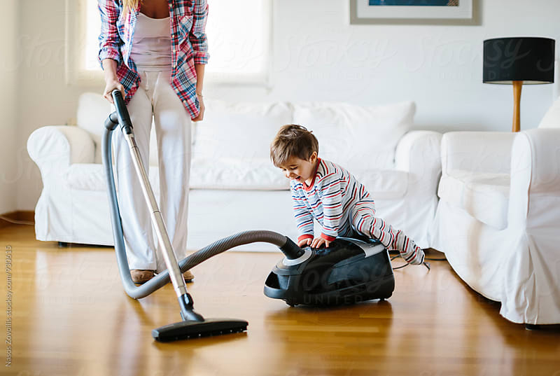 1 year old boy playing with a vacum cleaner by Nasos Zovoilis for Stocksy United