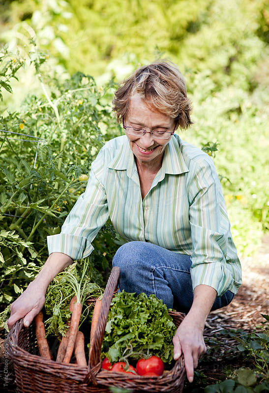 Senior Woman with Fresh Carrots and Tomatoes by Tyler Olson for Stocksy United