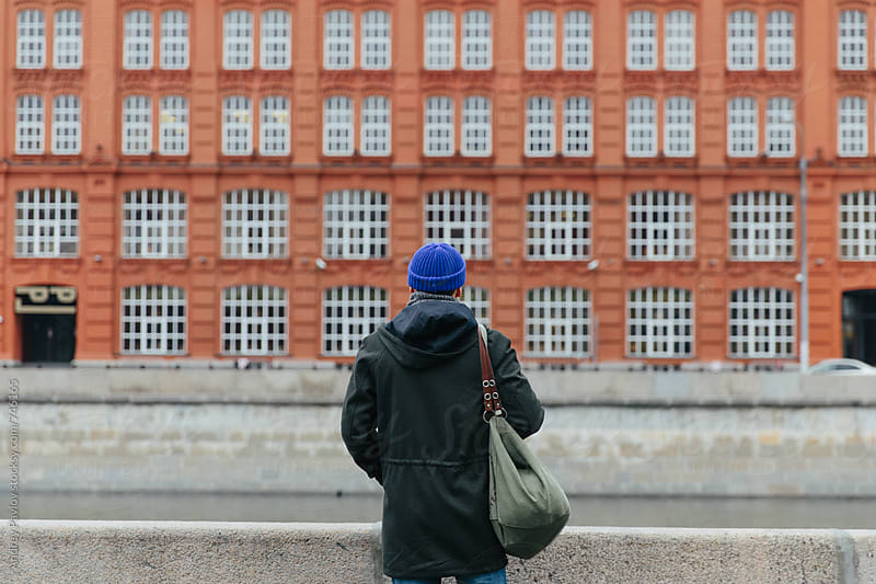 Man looking at the red building by Andrey Pavlov for Stocksy United