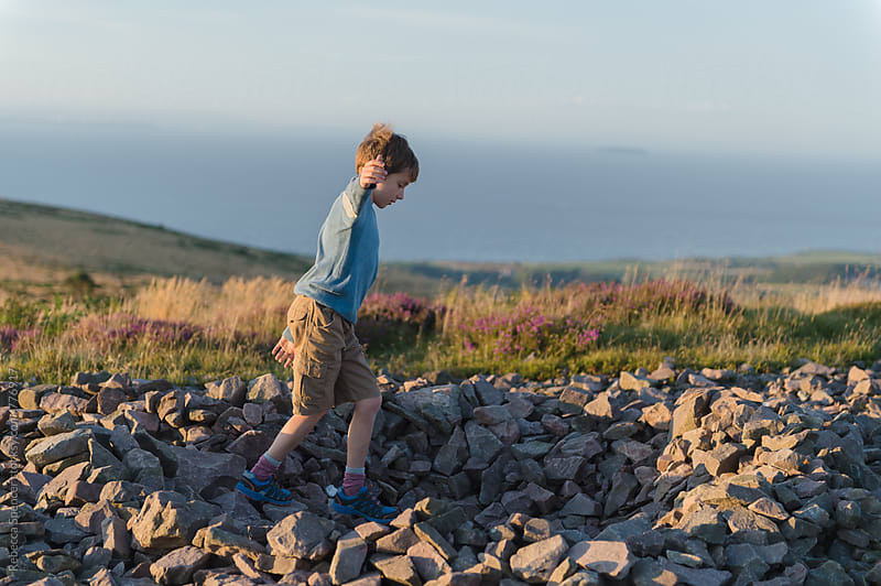 Boy at play building rock structure by Rebecca Spencer for Stocksy United