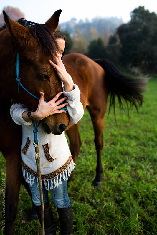 Woman embracing her affectionate horse by michela ravasio for Stocksy United