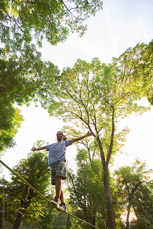Young man with arms outstretched balancing on a high slackline by RG&B Images for Stocksy United