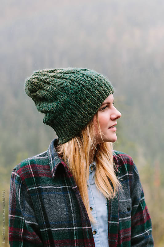 Young Blonde Woman Wearing Beanie And Flannel Standing Outside In Forest by Luke Mattson for Stocksy United