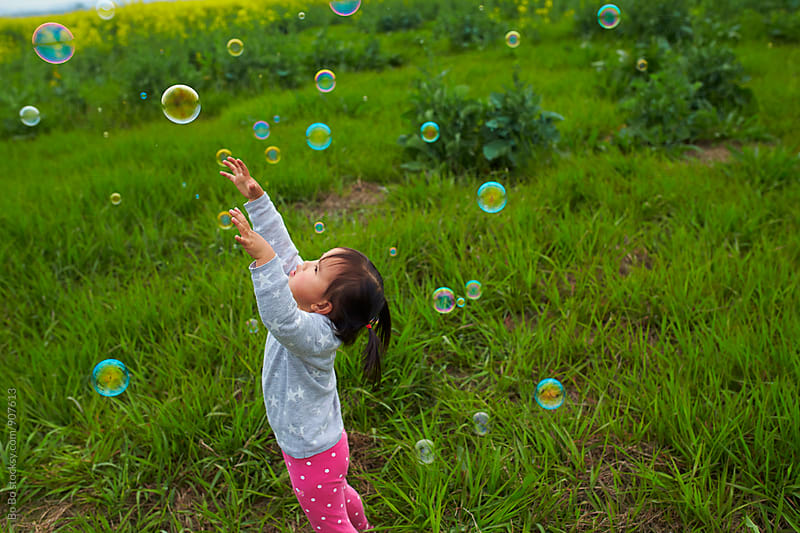 little asian girl playing with soap bubble outdoor  by cuiyan Liu for Stocksy United