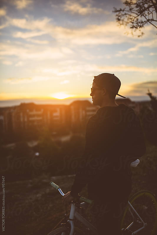 Young Man Looking at Sunset During a Bicycle Ride by VICTOR TORRES for Stocksy United