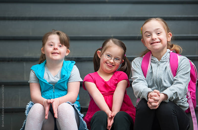 Adorable Elementary Aged Children with Down Syndrome on School Steps by Brian McEntire for Stocksy United