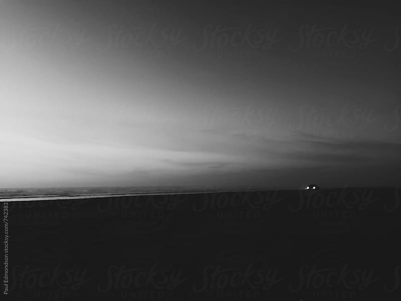 Headlights from car driving on beach at dusk by Paul Edmondson for Stocksy United