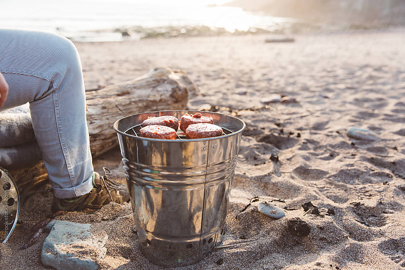 Burgers grilling on a bucket BBQ on a beach at sunset. by Helen Rushbrook for Stocksy United