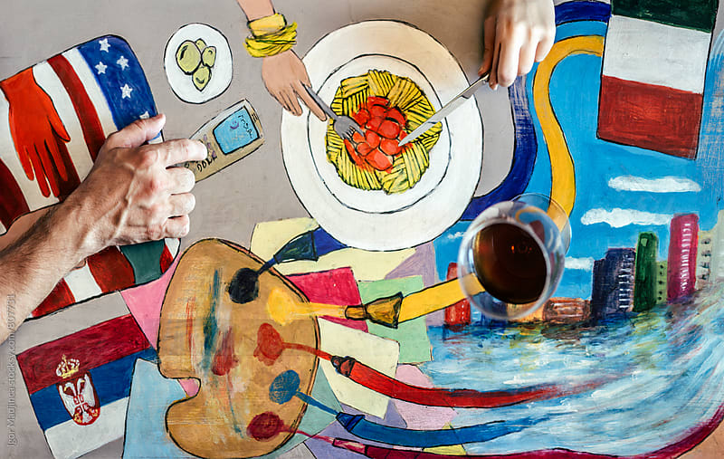 family table with many elements, food, mobile phone,hands, flags,palette of colors by Igor Madjinca for Stocksy United