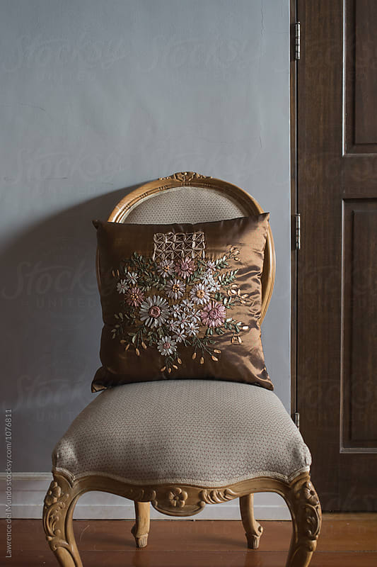 European style chair and pillow with intricate embroidery. by Lawrence del Mundo for Stocksy United
