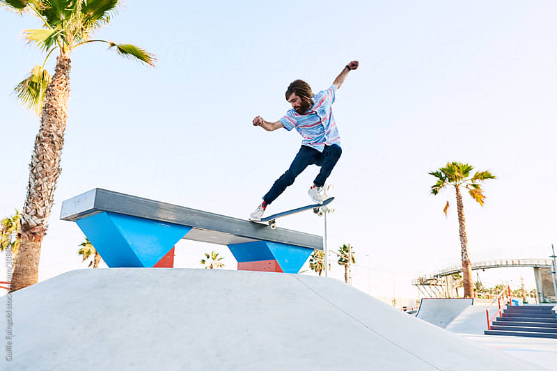 Bearded skater performing trick in skate park with arms widened by Guille Faingold for Stocksy United
