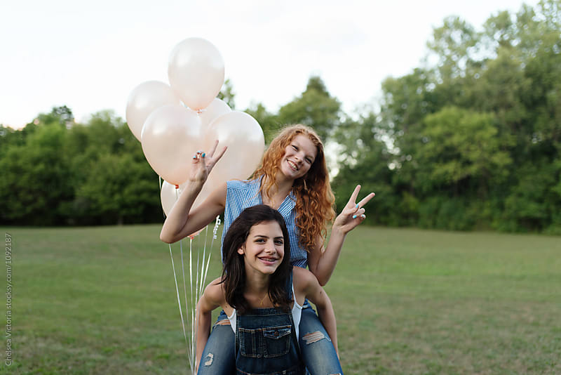 Two best friends outside playing with balloons by Chelsea Victoria for Stocksy United