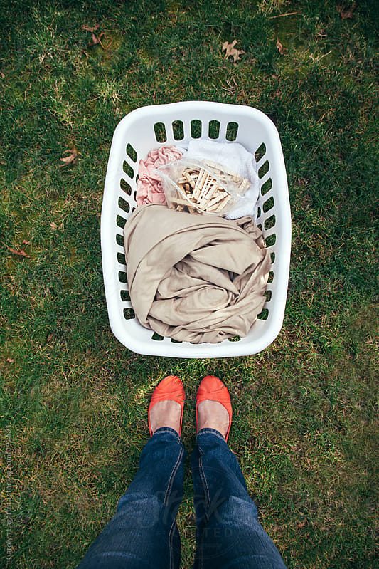 Standing outside above a freshly dried basket of laundry and clothes pins by Carolyn Lagattuta for Stocksy United