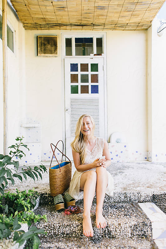 Beautiful blond woman sitting in front of the beach house by Nabi Tang for Stocksy United
